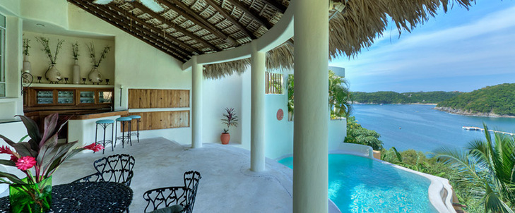 Villa terrace view and infinity pool overlooking Santa Cruz Bay, village and Pacific Ocean.