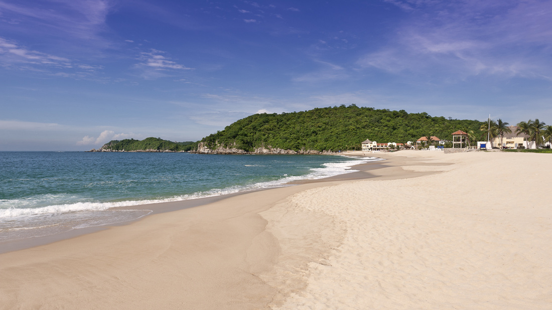 Under clear skies the turquoise blue  waters of the Southern Pacific Ocean lap on the pristine white sand of Chahué beach in Huatulco, Oaxaca, Mexico.