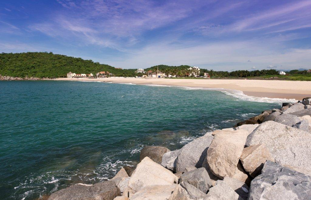 Chahue beach in Huatulco with crystal clear blue waters, white sand and sunshine.